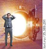 Businessman in front of banking vault door. Стоковое фото, фотограф Elnur / Фотобанк Лори