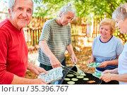 Senioren als Freunde oder Rentner grillen zusammen auf einer Gartenparty... Стоковое фото, фотограф Zoonar.com/Robert Kneschke / age Fotostock / Фотобанк Лори