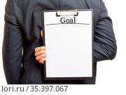 Business Mann im Anzug hält Klemmbrett mit Überschrift Goal als Planung... Стоковое фото, фотограф Zoonar.com/Robert Kneschke / age Fotostock / Фотобанк Лори
