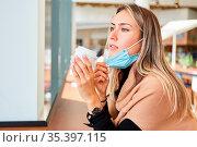 Frau mit Mundschutz am Kinn im Cafe bei einem Coffee to Go bei Covid... Стоковое фото, фотограф Zoonar.com/Robert Kneschke / age Fotostock / Фотобанк Лори