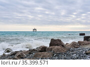 Winter beach with seascape and a rickety structure on the stilts of an aquaculture farm in the distance. Стоковое фото, фотограф Евгений Харитонов / Фотобанк Лори