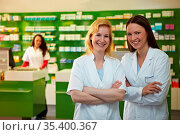 Zwei lachende Apothekerinnen stehen zufrieden in einer Apotheke. Стоковое фото, фотограф Zoonar.com/Robert Kneschke / age Fotostock / Фотобанк Лори