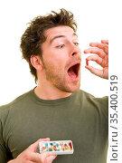Junger Mann schluckt eine rote Pille und hält Tabletten in einer ... Стоковое фото, фотограф Zoonar.com/Robert Kneschke / age Fotostock / Фотобанк Лори