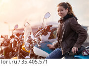 Motorcycle girl wearing brown leather jacket sitting on her motorbike, looking at camera. Стоковое фото, фотограф Кекяляйнен Андрей / Фотобанк Лори