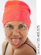 Cheerful Caucasian woman showing tongue, facial portrait, female wearing red headscarf. Стоковое фото, фотограф Кекяляйнен Андрей / Фотобанк Лори
