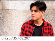Portrait of young handsome Filipino hipster man against concrete wall... Стоковое фото, фотограф Zoonar.com/Toni Rantala / easy Fotostock / Фотобанк Лори