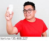 Studio shot of young handsome overweight Filipino man against white... Стоковое фото, фотограф Zoonar.com/Toni Rantala / easy Fotostock / Фотобанк Лори