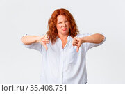 Disgusted middle-aged redhead woman, female entrepreneur grimacing... Стоковое фото, фотограф Zoonar.com/Seva Levitsky / easy Fotostock / Фотобанк Лори
