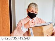 Frau mit Mundschutz vor Wohnungstür gibt Lieferdienst eine Unterschrift. Стоковое фото, фотограф Zoonar.com/Robert Kneschke / age Fotostock / Фотобанк Лори