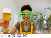 Mixed race woman celebrating st patrick's day making video call holding a beer. Стоковое фото, агентство Wavebreak Media / Фотобанк Лори