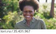 Portrait of smiling african american woman standing in sunny garden. Стоковое видео, агентство Wavebreak Media / Фотобанк Лори