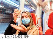 Fahrgast mit Maske beim Hände desinfizieren im Nahverkehr wegen Covid... Стоковое фото, фотограф Zoonar.com/Robert Kneschke / age Fotostock / Фотобанк Лори