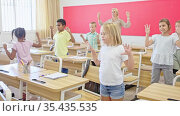 Cheerful preteen pupils doing little warm-up in class with female teacher at lesson in elementary school. Стоковое видео, видеограф Яков Филимонов / Фотобанк Лори