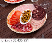 Appetizing cold cuts from Spanish ham, spicy dry-cured sausages and bacon on plate. Стоковое фото, фотограф Яков Филимонов / Фотобанк Лори