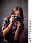 Девушка-фотограф выглядывает из-за фотоаппарата, поясной студийный портрет на сером фоне. Стоковое фото, фотограф Иванов Алексей / Фотобанк Лори