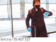 Reisender mit Maske wegen Covid-19 schaut auf seine Armbanduhr im... Стоковое фото, фотограф Zoonar.com/Robert Kneschke / age Fotostock / Фотобанк Лори