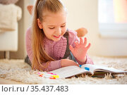 Kind macht Hausaufgaben für die Schule mit einem Schulbuch. Стоковое фото, фотограф Zoonar.com/Robert Kneschke / age Fotostock / Фотобанк Лори