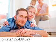 Vater liegt mit seiner Tochter vor der restlichen Familie im Wohnzimmer. Стоковое фото, фотограф Zoonar.com/Robert Kneschke / age Fotostock / Фотобанк Лори
