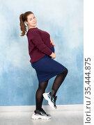 Pregnant woman in business clothing posing on blue background, holding her tummy. Стоковое фото, фотограф Кекяляйнен Андрей / Фотобанк Лори