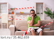 Young male student studying at home in self-isolation concept. Стоковое фото, фотограф Elnur / Фотобанк Лори