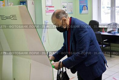 Пожилой пациент в поликлинике в маске