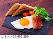 Fried eggs with bacon, toasted bread and tomatoes at plate, american breakfast. Стоковое фото, фотограф Яков Филимонов / Фотобанк Лори