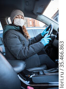 Young woman with surgery protective mask on her face and latex gloves is driving car. Virus protection. Стоковое фото, фотограф Кекяляйнен Андрей / Фотобанк Лори