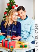 Glückliches lächelndes Paar beim Verpacken von Geschenken zu Weihnachten. Стоковое фото, фотограф Zoonar.com/Robert Kneschke / age Fotostock / Фотобанк Лори