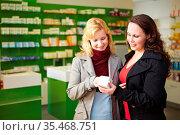 Zwei Frauen stehen mit Medikament in einer Apotheke. Стоковое фото, фотограф Zoonar.com/Robert Kneschke / age Fotostock / Фотобанк Лори