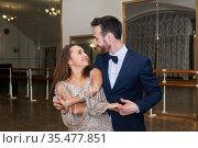 Man and woman dance, looking at each other, in an empty ballroom. Стоковое фото, фотограф Евгений Харитонов / Фотобанк Лори