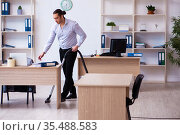 Young male employee cleaning office during pandemic. Стоковое фото, фотограф Elnur / Фотобанк Лори