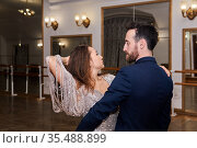 Man and woman dancing expressive partner dance in empty ballroom. Стоковое фото, фотограф Евгений Харитонов / Фотобанк Лори