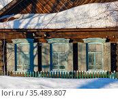 Покрытый снегом старый бревенчатый дом с деревянными ставнями и замерзшими окнами. Поселок Висим, Урал, Свердловская область, Россия. Стоковое фото, фотограф Bala-Kate / Фотобанк Лори
