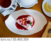 Piece of ice cream cake with berry topping and candied cherry. Стоковое фото, фотограф Яков Филимонов / Фотобанк Лори