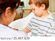Kinderarzt bindet Verband um Arm oder Handgelenk von Kind bei Verstauchung. Стоковое фото, фотограф Zoonar.com/Robert Kneschke / age Fotostock / Фотобанк Лори