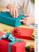 Alte Hände einer Seniorin packen Geschenk ein zu Weihnachten. Стоковое фото, фотограф Zoonar.com/Robert Kneschke / age Fotostock / Фотобанк Лори
