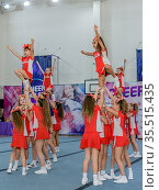 Moscow, Russia - December 22, 2019: caucasian girls of school age in red uniform show trick at cheerleading competitions. Редакционное фото, фотограф Андрей Копылов / Фотобанк Лори