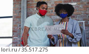 Diverse male and female fashion designers wearing face masks in discussion at work looking at paper. Стоковое видео, агентство Wavebreak Media / Фотобанк Лори
