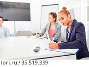 Geschäftsfrau als Trainee in der Ausbildung macht sich Notizen in... Стоковое фото, фотограф Zoonar.com/Robert Kneschke / age Fotostock / Фотобанк Лори
