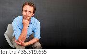 Business Mann sitzt entspannt und stützt das Kinn auf eine Hand. Стоковое фото, фотограф Zoonar.com/Robert Kneschke / age Fotostock / Фотобанк Лори