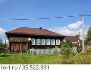 Старинный ухоженный бревенчатый жилой дом с потемневшим от времени фасадом. Поселок Висим, Средний Урал, Свердловская область. Стоковое фото, фотограф Bala-Kate / Фотобанк Лори