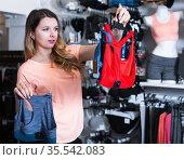 Smiling girl customer choosing sports underwear. Стоковое фото, фотограф Яков Филимонов / Фотобанк Лори
