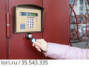 Person with wireless key touching intercom for house access, close-up view. Стоковое фото, фотограф Кекяляйнен Андрей / Фотобанк Лори