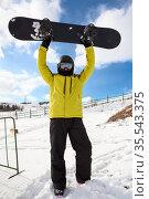 Happy Caucasian male snowboarder wearing helmet and glasses, full length portrait over blue sky in mountains rising up his board. Стоковое фото, фотограф Кекяляйнен Андрей / Фотобанк Лори
