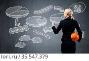 Businesswoman draws various business infographics on blackboard. Back... Стоковое фото, фотограф Zoonar.com/Aleksandr Khakimullin / easy Fotostock / Фотобанк Лори