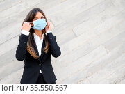 Elegant Businesswoman put on protective face mask outdoors. COVID... Стоковое фото, фотограф Zoonar.com/DAVID HERRAEZ CALZADA / easy Fotostock / Фотобанк Лори