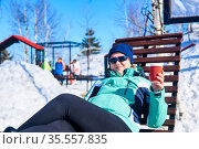 Woman with a cup of hot drink lies in a sun lounger outdoors on a cold winter day. Стоковое фото, фотограф Евгений Харитонов / Фотобанк Лори