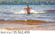 young man splashing wave of the Volga river against the background of the Zhiguli mountains on a summer sunny day. Стоковое фото, фотограф Акиньшин Владимир / Фотобанк Лори