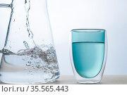 Water into the green glass on white background. Стоковое фото, фотограф Александр Иванов / Фотобанк Лори