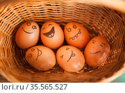 Stack of eggs with hand drawn faces on straw basket, easter preparation, holiday mood concepts. Стоковое фото, фотограф Ольга Балынская / Фотобанк Лори